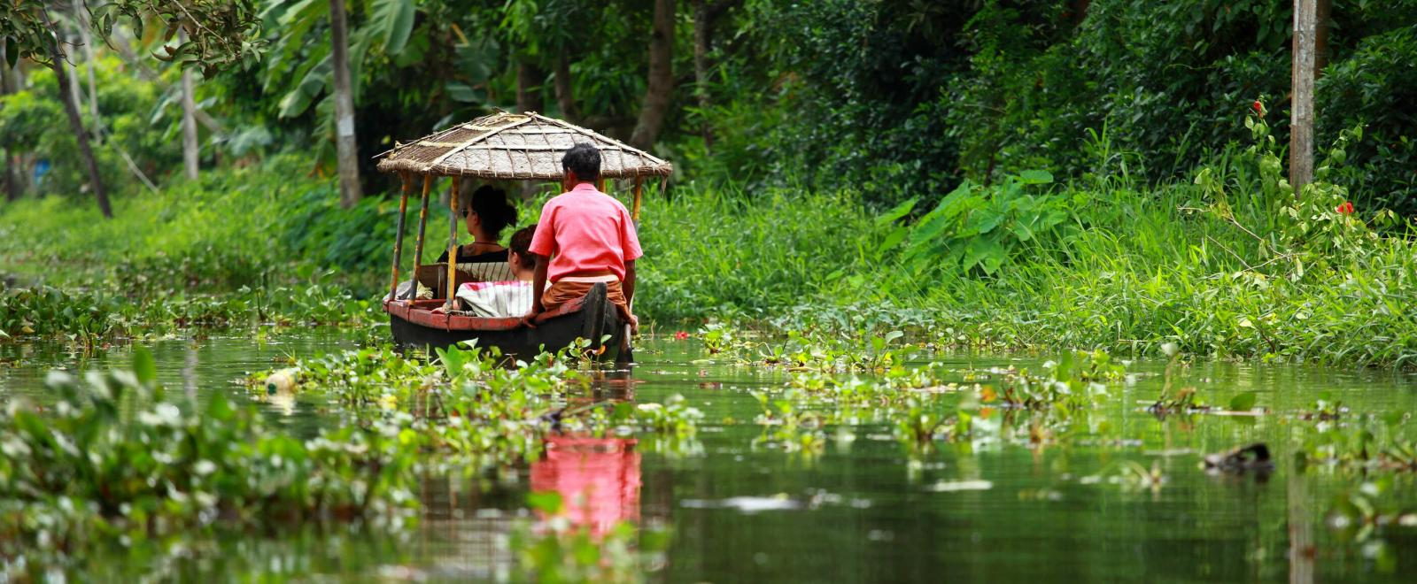 Local man take a boat on the water in the Kerala Backwaters in India.